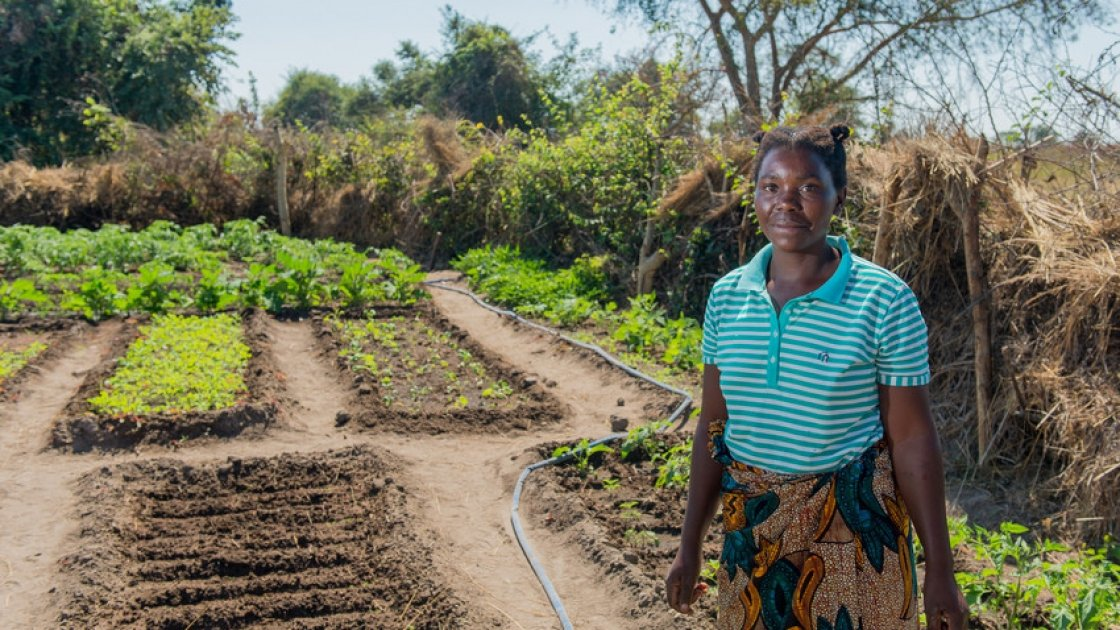 Queen, 36, a participant in Concern's RAIN programme stands in her vegetable garden. She has received tools, seeds, livestock and training. Photo: Gareth Bentley / Concern Worldwide.