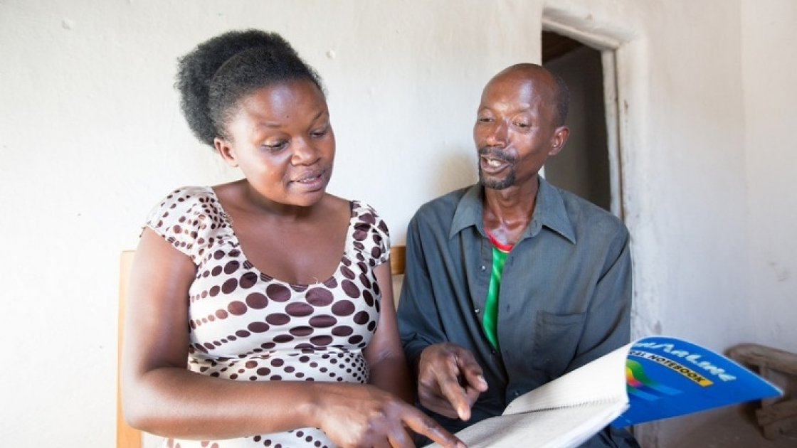 Stanislas Iriboneye participated in Concern's Graduation programme in Rwanda. He is pictured here with his case worker, Gisèle Umumararungu, who is reviewing his financial plans. Photo: Robin Wyatt / Concern Worldwide, 2015.