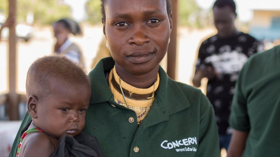 Chan Adim Garang, is one of twins admitted to the outpatient therapeutic programme (OTP) run by Concern in Maduany in Aweil North, South Sudan. Pictured here with Monica Mawien a supervisor with the Concern community nutrition team. Photographer: Kieran M
