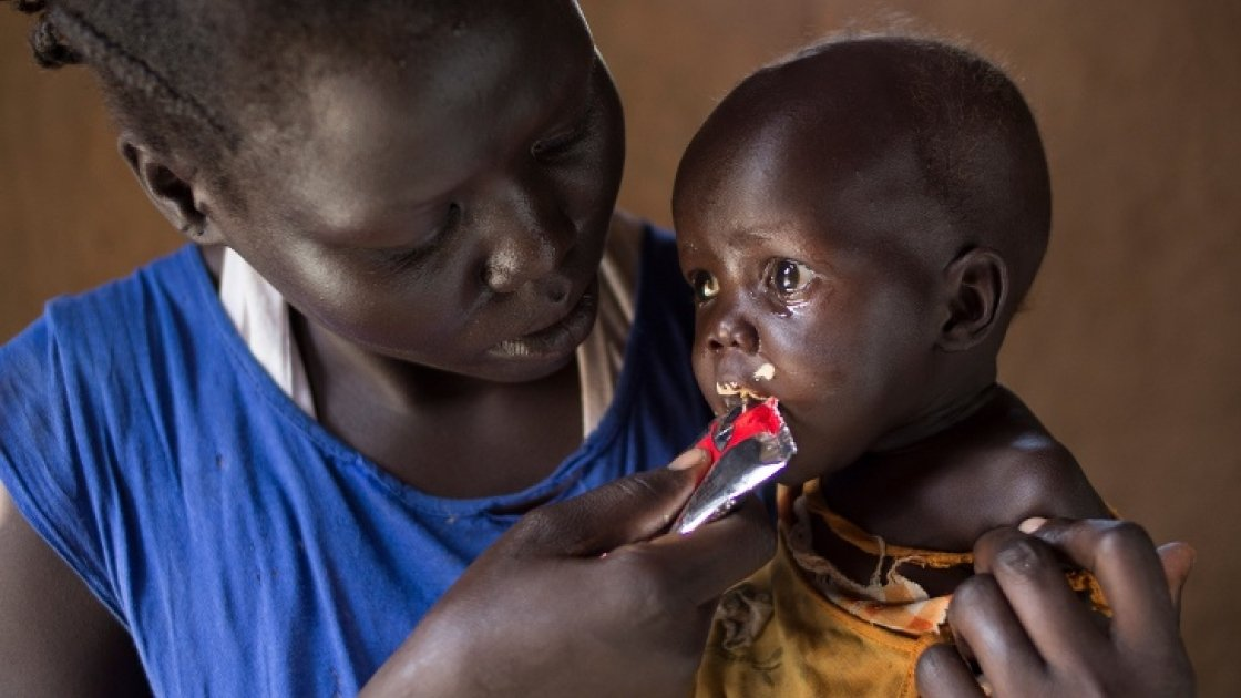 Aweng Ayii (25) and her 10-month-old daughter, Adut Ayii Garang,at their home in Nyamel, Northern Bahr el Ghazal in South Sudan. Aweng is feeding her ready-to-eat therapeutic food (RUTF), supplied as part of the programme. Photo: Kieran McConville/Concern