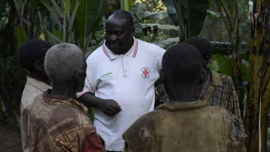 Concern Project Supervisor Joseph Nkengurukiyimana talks to members of the marginalised Batwa community outside their homes on a remote hillside of Kabere, Mabayi, Cibitoke, Burundi.