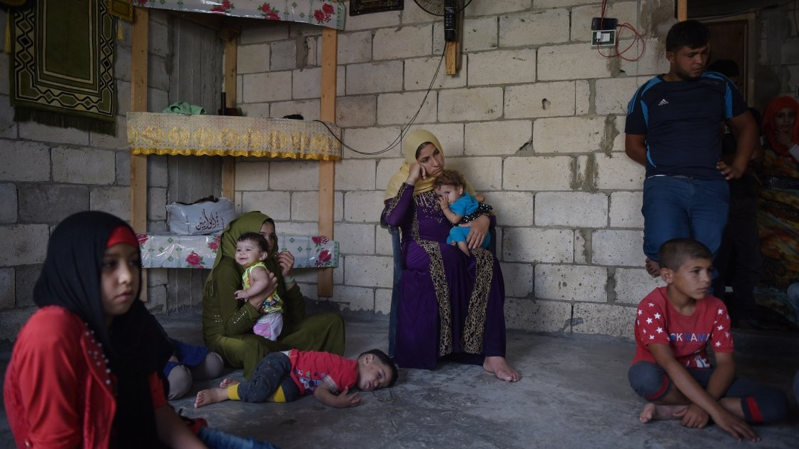 *Kafya, 30, centre, sits with her family who all share a house which Concern will be fitting with windows and doors, in Northern Lebanon. Photograph by Mary Turner/Panos Pictures for Concern Worldwide  *name changed for security reasons