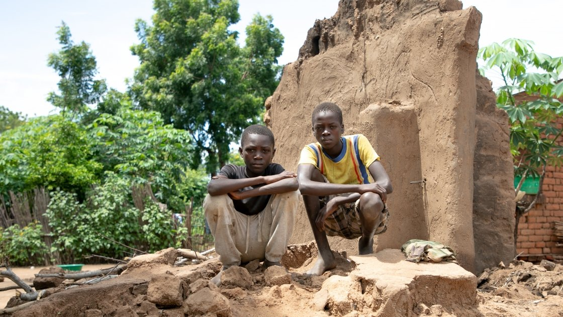 Brothers, Charity(16) and Fraction (14) standing on what's left of their home. Their home was washed away with all their belongings. The brothers family are casual labourers. With no crops to harvest, his parent won't have any work this season.  Location: