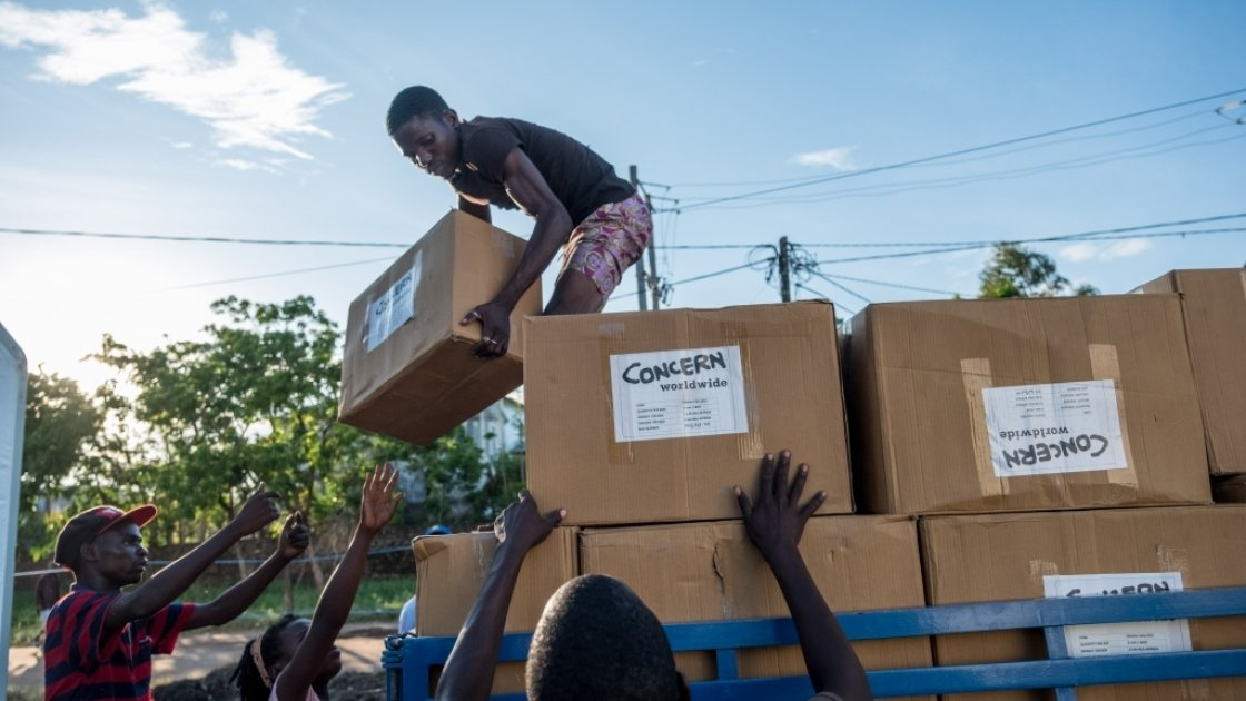 """Esparanza Maria, a 25-year-old day worker from Nhamatanda, helps load boxes containing essential household supplies from a warehouse to a truck. The items will be distributed the next day in the village of Ndeja. """"It makes me feel good to be able to help"""