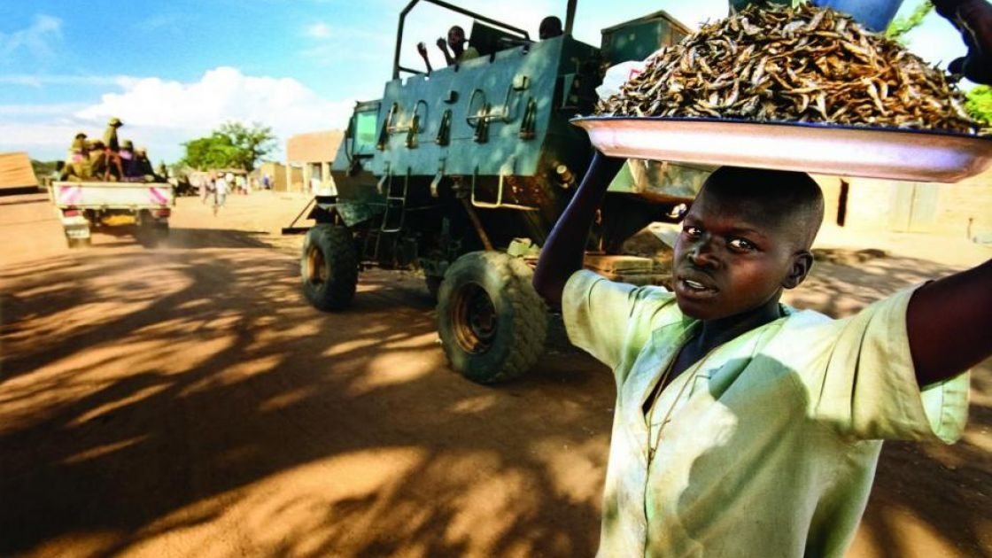 A boy sells dried fish in a camp for internally displaced people in Uganda in 2003. Photo: Concern Worldwide.