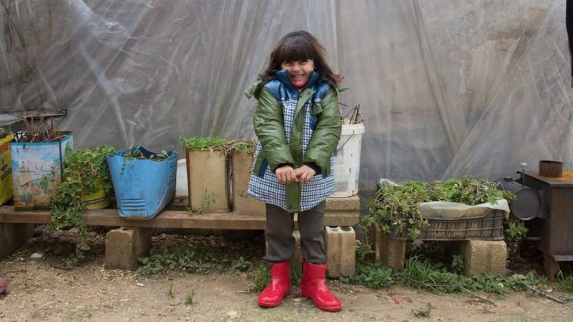 Syrian refugee Ola, wears her winter clothes that were distributed to her by the Concern team at the informal tented settlement in the village of Bebnine, in Akkar, north of Lebanon. Photographer: Dalia Khamissy