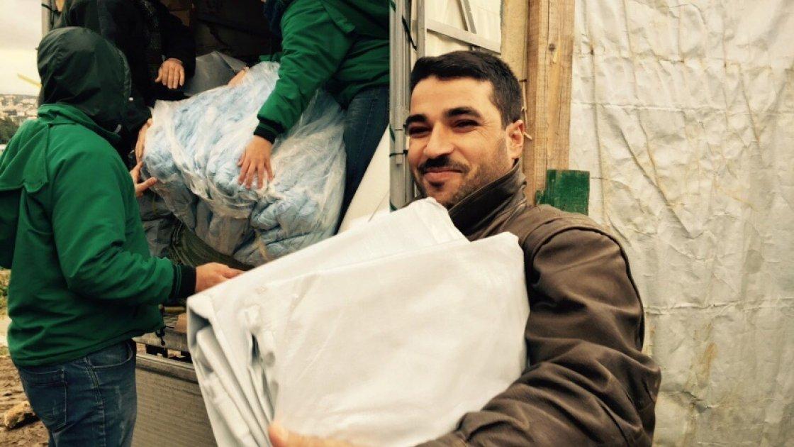 Ahmad el Ezzou receiving Non Food Items in Minyara El Ehssan Informal Settlement, Akkar, Lebanon Photographer: Amanda Ruckel/January 2015/ Lebanon.jpg