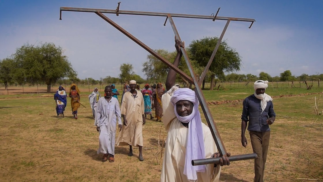 Osman Zakaria carries a planting tool to the conservation agriculture demonstration plot at Ridjil Dour village in Chad.