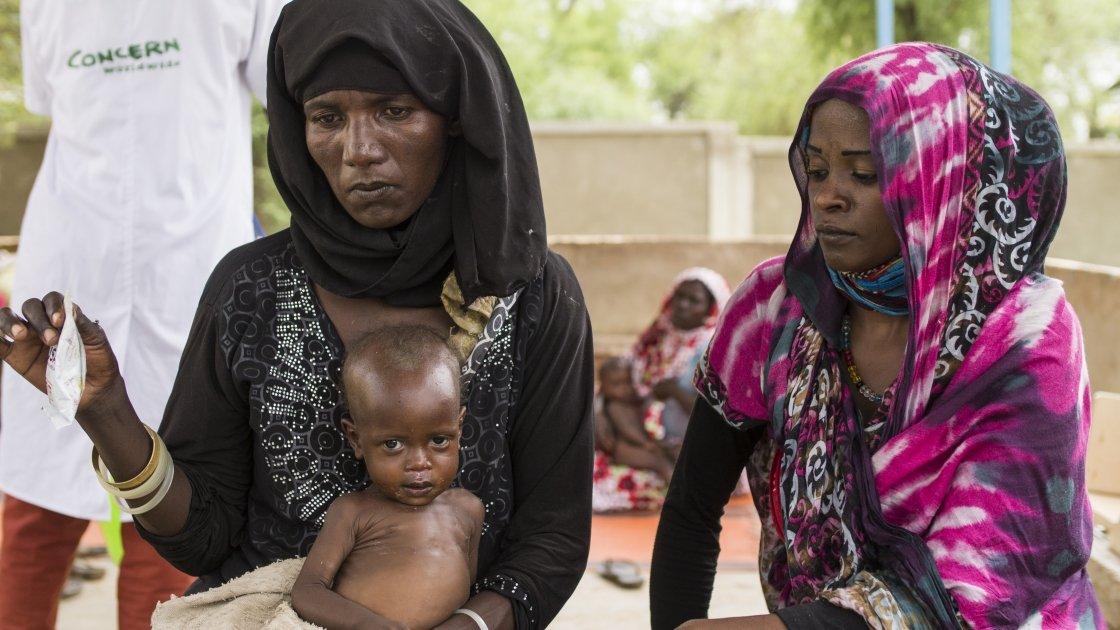 Health volunteer, Iklass Mahamat Tom, accompanies neighbor Fatime and her infant daughter, Falmata, to a health clinic in Koutoufou, Chad.