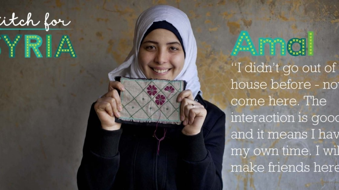 Stitch for Syria: Amal holding up a cross stitch pattern. Credit: Abbie Trayler-Smith/Panos Pictures for Concern Worldwide