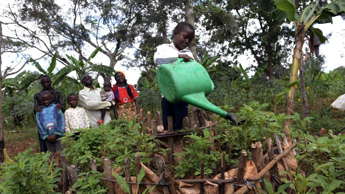 Victoria Macumi's son is watering their kitchen garden in Burundi