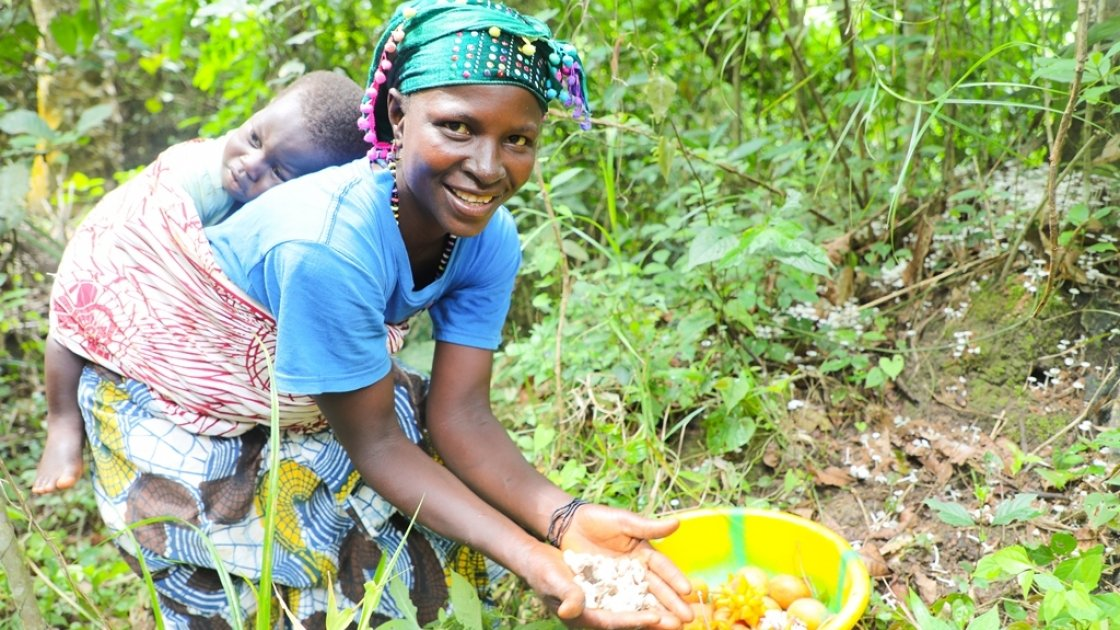 Kadiatu Bangura (35) with son Sheku Conteh (1) picking orange wild fruits in the local forest. She is a participant of the LANN programme run by Concern Worldwide and Welthungerhilfe in Sierra Leone. Photo: Jennifer Nolan / Concern Worldwide.