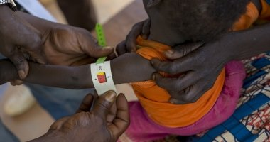 A health worker at a Concern-supported clinic at Gbadengue carries out a regular health assessment of 17-month-old Nicoles. She was diagnosed as severely malnourished two weeks ago. Since then, she has put on more than half a kilo. Photographer: Chris de Bode