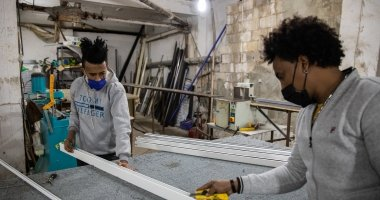 Two Ethiopian apprentices in a workshop, measuring a frame