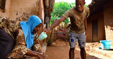 Marriam Jamali's son Bruno helps pour water on her hands while she washes them. They received soap as part of hygiene distribution to help prevent the spread of Covid-19 in Malawi.