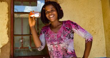 Smiling young woman Alice Eneya holds up soap she received from Concern.