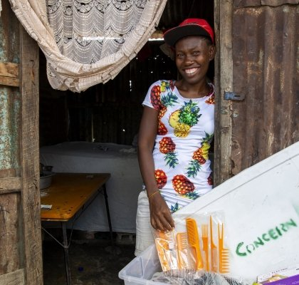 Fridna Dimanche 27, a beautician and hairdresser, stands smiling next to her cosmetics box at her home in Cité Soleil, one of the poorest communities in Haiti. Photo: Dieu Nalio Chery/ Concern Worldwide