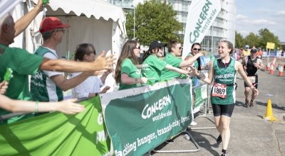 Concern runner at the AJ Bell London Triathlon being cheered on by Concern supporters