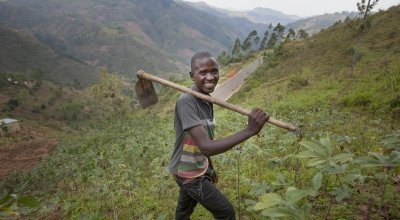 Gerard Ndabahekeye (28) with his new hoe bought with the profits of his business, a small shop, which he was able to set up due to the investment of the Graduation Programme. Photographed in his cassava field near his home in Bukinanyana, Cibitoke, Burundi. Photo: Abbie Trayler-Smith / Concern Worldwide