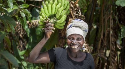 Meresiyana Cimpaye with the Banana Trees she bought from the profits of her Graduation Programme cash transfer, at her home in Bukinanyana, Cibitoke, Burundi. Photo: Abbie Trayler-Smith / Concern Worldwide