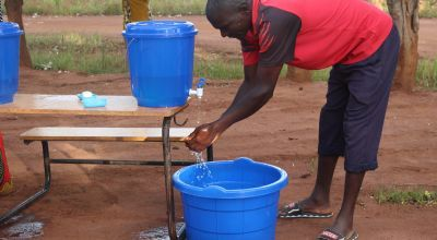 Enika Mussa  practices good hand washing to prevent the spread of Covid-19. He is attending the Concern Consumption (Cash) Support Distribution through he Graduation Programme in Mangochi District, Malawai. Photo: Levy Mwambarulu Kadrab / Concern Worldwide