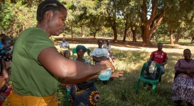 Agness, a Community Health Volunteer demonstrating how she will teach people handwashing. Photo: Henry Mhango