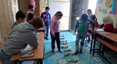 Children enrolled in the non-formal education (NFE) programme in the 'Make Math Fun' class in Northern Syria, January 2020. This is part of the numeracy sessions to learn multiplication using small coloured balls.