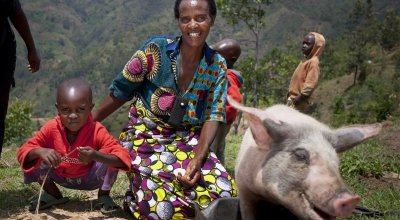 Violette and her son Lievain with the pig she has bought from the profits of her business at her home in Cibitoke, Burundi.  Photo: Abbie Trayler-Smith / Concern Worldwide