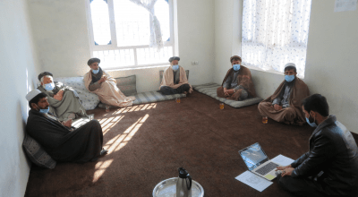Men sit socially distanced in a meeting room