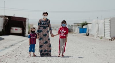 Sheren stands in the street outside their tent with her two daughters in Khanke camp. Photo: George Henton