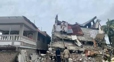 A hotel owner and friend, stand in front of the now crumbled hotel building, several people inside died or suffered severe injury. Haiti Photo: Makayla Palazzo