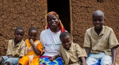 Beatrice Mukandagano, a beneficiary of the Graduation model programme in Kirundo province (Burundi) sitting with her 4 children beside the house she built herself in Bugabira commune. She also bought land to cultivate as a result of the programme.