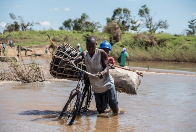 Zaccharia Roberto pushes his bicycle laden with charcoal across a flooded river near Nhamatanda, Mozambique. Cyclone Idai has disrupted infrastructure across the country, impacting livelihoods and hampering aid efforts. Photo: Tommy Trenchard / Concern Worldwide